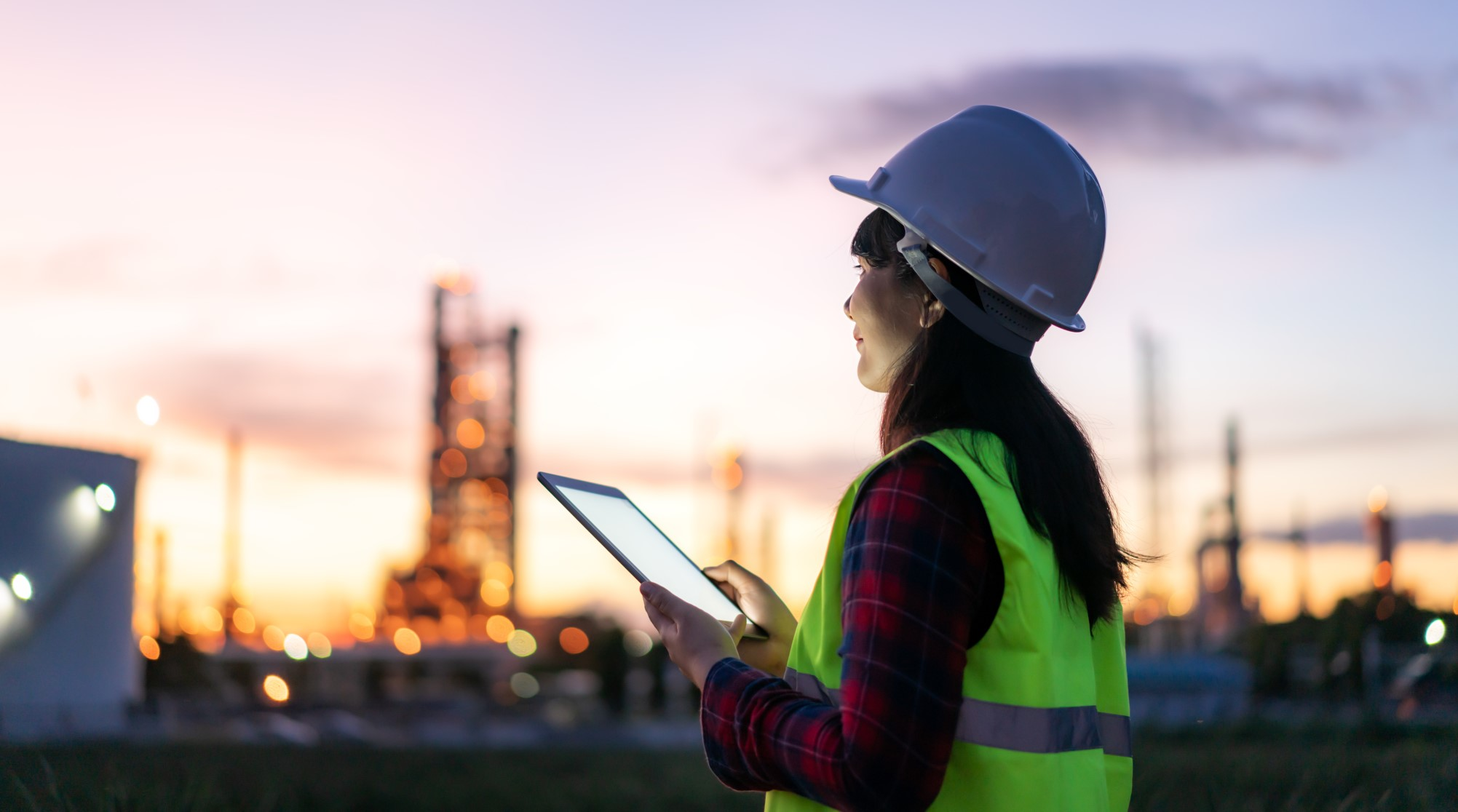 Woman holding tablet at construction site while the sun is setting.
